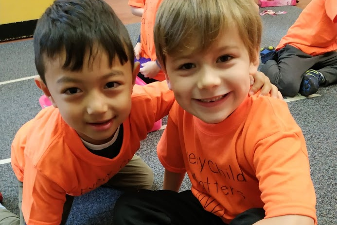 "To mark Orange Shirt Day, students wrote ""every child matters"" and traced their handprint on an orange shirt before undertaking a neighbourhood walk to raise awareness of residential schools."